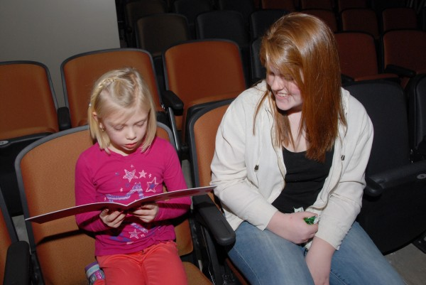 Riley Thurston, a junior at Brewer High School, sits beside Brewer Community School first-grader Lauren and listens as she reads her story book during an assembly at the Brewer Performing Arts Center. Kate wrote a letter to BHS students enrolled in creative writing classes taught by Michelle Macdonald and Kevin Napolillo. Thurston transformed Lauren's letter into a story book in which Lauren is the main character, a famous ballerina.