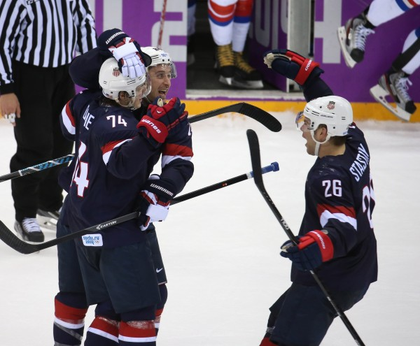 Team USA mobs forward T.J. Oshie (74) after he scored to win a shootout against Russia in a men's hockey game at Bolshoy Ice Dome during the Winter Olympics in Sochi, Russia, Saturday, Feb. 15, 2014. USA defeated Russia, 3-2.