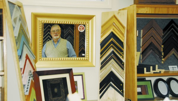 Founder Ed Perkins is reflected in a framed mirror by the front desk at his School Street Picture Framing in Brewer. The shop has 3,000 in-store corner-frame samples, some of which are seen in this picture.