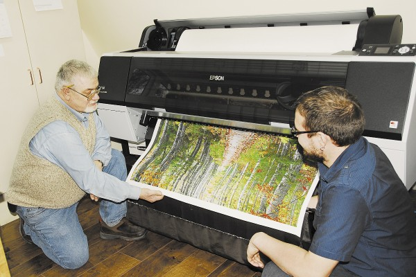 Ed Perkins (left) and Adam Perkins inspect an image coming out of an Epson 9900 printer. Printed on 44-inch-wide canvas, this autumn image from Acadia National Park looks almost like a painting. The printer works on the same principle as a desktop inkjet printer, but the ink is of much higher quality. It will resist fading for upwards of 100 years or more, retains color vibrancy, and is water resistant.