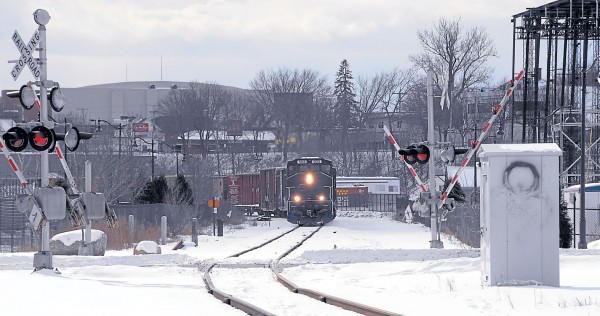 Its headlights glowing, Pam Am Railways Locomotive 503 pulls a long line of cars north through Bangor Waterfront Park in early afternoon on Feb. 10. The warning lights blink as the crossing arms drop where the railroad tracks cross Railroad Street.