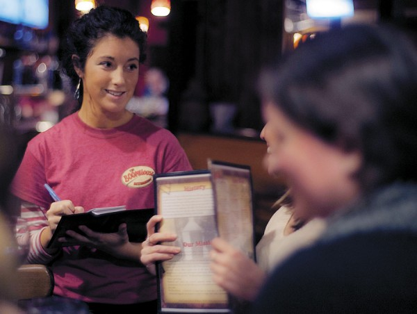 Waitress Aline Michaud smiles as she talks with patrons Friday at the BoomHouse Restauant in Old Town.