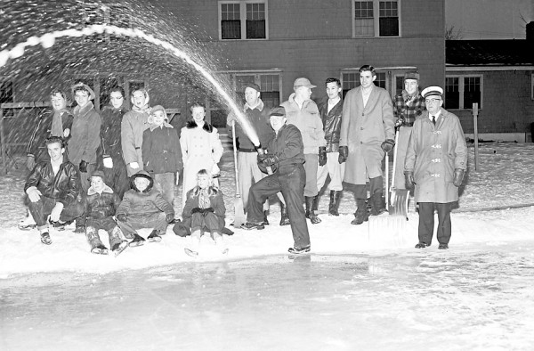 Dow Air Force Base Firemen spent Monday afternoon, Jan. 2, 1956, making a skating rink for the children of the base personnel. Shown above as a group of the youngsters watch, left to right, are Fire Chief James F. LaFountain (holding broom), S-Sgt. Harry E. Guinn, Pennsylvania; S-Sgt. Stanley Moczewski, Pennsylvainia; S. Sgt. Stanley H. Rouff, Indiana; S-Sgt. Dan Billips, Virginia; T-Sgt. David Dowty, Texas; and Assistant Fire Chief Jullian S. White.