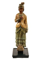 Carved ship's figurehead in the form of a woman in fancy coat with feathered hat, made circa 1880, that brought $11,500