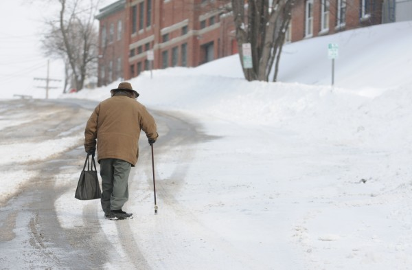 An older man makes his way up a snow-covered Center Street in downtown Bangor on Sunday morning.