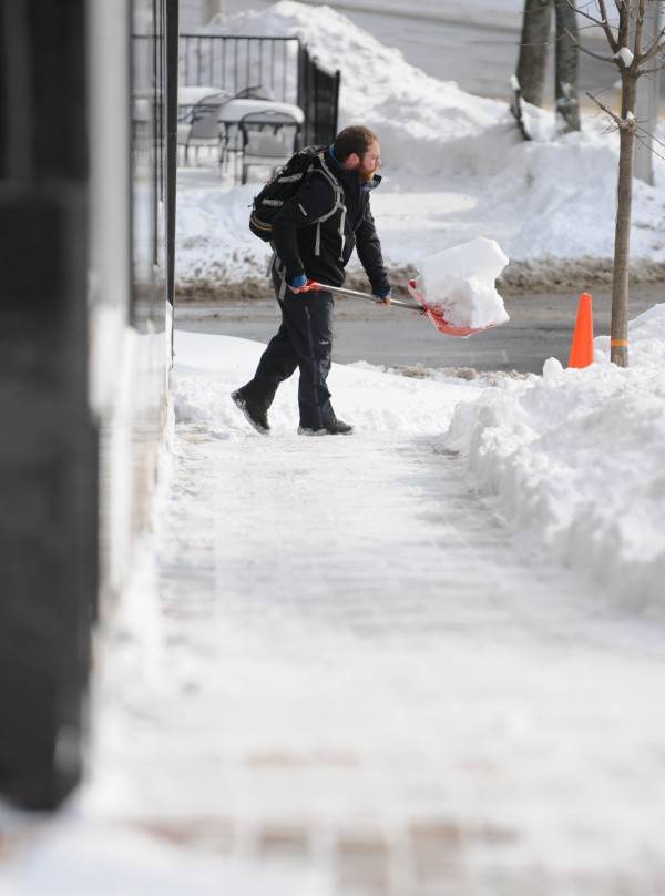 The sidewalk along Hammond Street is cleared of snow by a man in downtown Bangor on Sunday morning.