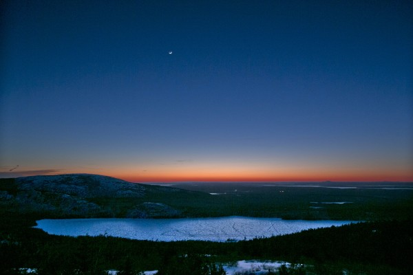 A tiny crescent moon hangs in the sky above Eagle Lake at sunset in this view from Cadillac Mountain at Acadia National Park