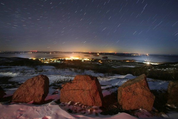 Stars wheel through the evening sky in a time exposure overlooking Bar Harbor from Cadillac Mountain at Acadia National Park.