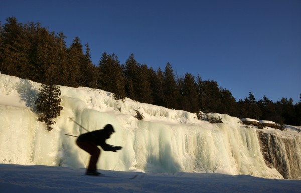 A skier passes a 30-foot-high, 200-foot-long wall of ice alongside the Cadillac Mountain Road in Acadia National Park.