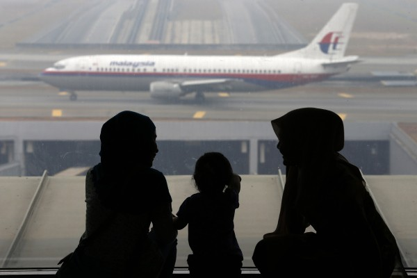 Women and a girl look at a Malaysia Airlines plane on the tarmac of Kuala Lumpur International Airport on Thursday. Search planes found no sign on Thursday of the missing Malaysia Airlines aircraft, Flight MH370, in an area where satellite images had shown debris, taking the as-yet fruitless hunt into the sixth day.