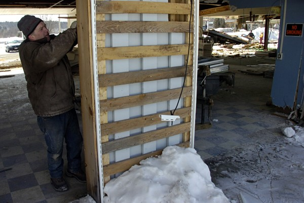 James Bernadini of East Millinocket works at pulling apart a section of The Hamlet building on Friday.