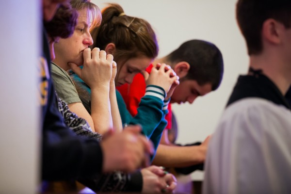 DeLayne Daldeman, from left, Samantha Valencia, Breanna Valencia, 15, Felipe Valencia Jr., 18, pray during Sunday church service at Saint John Mary Vianney Catholic Church, in Darrington, Wash., on Sunday, March 30, 2014.