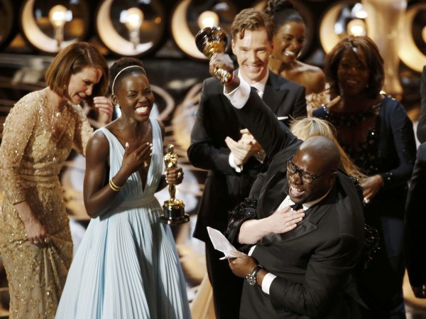 Director and producer Steve McQueen (R) celebrates after accepting the Oscar for best picture for his film &quot12 Years a Slave&quot, with actress Lupita Nyong'o (L), at the 86th Academy Awards in Hollywood, California March 2, 2014.