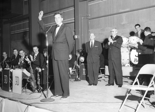Governor Edmund S. Muskie, left, addresses 5,000 people at the Bangor Auditorium as, left to right, Chamber of Commerce secretary Norbert X. Dowd,  Tommy Dorsey, Louis Bellson and Jimmy Dorsey (back to camera) look on.
