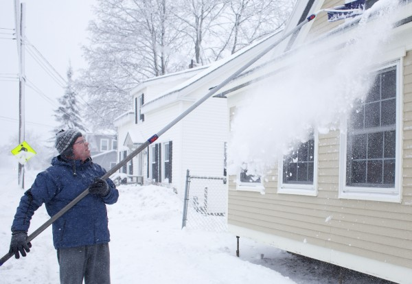 Nathan Dusablon rakes the snow off his roof at his home on Hammond Street in Bangor. Dusablon, who started removing snow around his home at 6 a.m., said, &quot I'm going to give in and buy a snowblower when they go on sale.&quot A late winter storm brought 11 inches of snow to Bangor by Thursday morning.