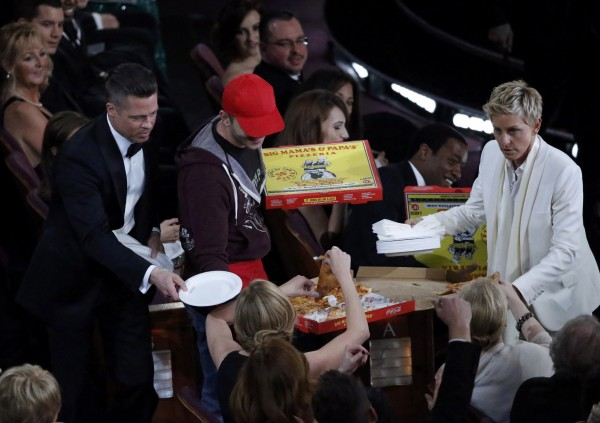 Show host Ellen DeGeneres (R) delivers pizza to the audience as actor Brad Pitt (L) hands out paper plates at the 86th Academy Awards in Hollywood, California March 2, 2014.