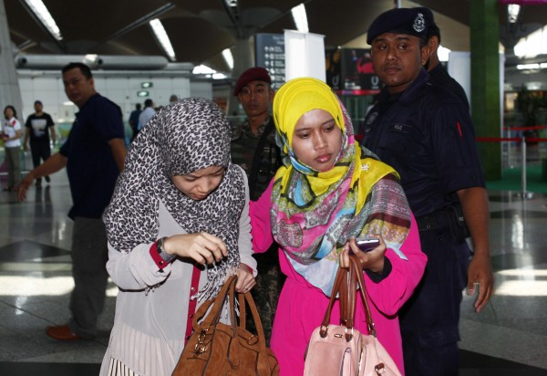 Family members of those onboard the missing Malaysia Airlines flight walk into the waiting area at Kuala Lumpur International Airport in Sepang March 8, 2014. The missing Malaysia Airlines flight was carrying 152 Chinese, 38 Malaysians, 12 Indonesians, seven Australians and three Americans among the 227 passengers, the airline said Saturday.