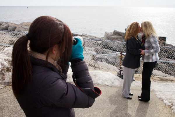 Photographer Tricia Jamiol captures a post wedding ceremony kiss between Kandis Stanley (right) and Jen Gibson at Portland Headlight in Cape Elizabeth on Monday. The pair traveled from New Orleans to get married in Maine.