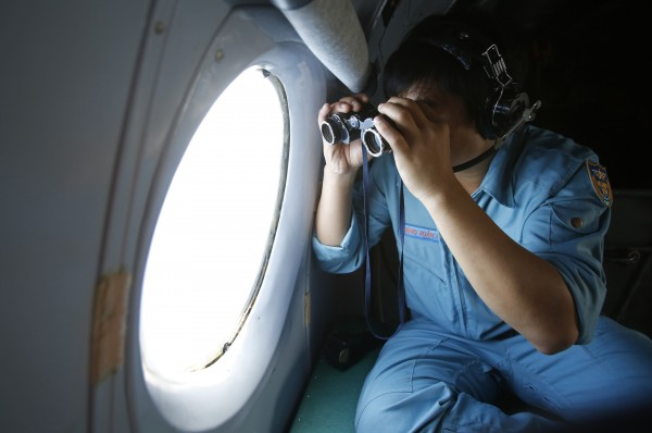 On Wednesday, military officer Dang Xuan Hung looks out a window of a Vietnam Air Force aircraft AN-26 during a mission to find the missing Malaysia Airlines flight MH370, that disappeared from radar screens in the early hours of Saturday, off Con Dao island.