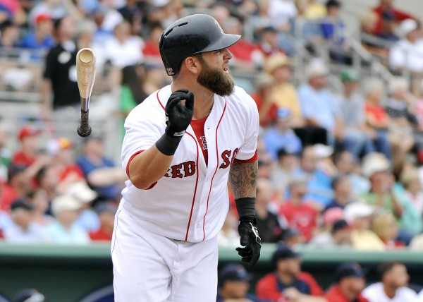 Boston Red Sox first baseman Mike Napoli (12) flips his bat after hitting a solo home run against the Minnesota Twins during their game at JetBlue Park on Saturday.