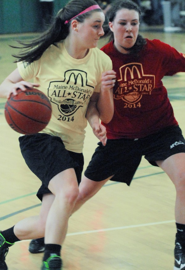 Allie Clement of McAuley High School and the West team (left) tries do break through the defense of East defender Hannah Shaw of Mount Desert Island during the McDonald's East-West Senior All-Star Basketball Games at at Husson University in Bangor on Saturday.