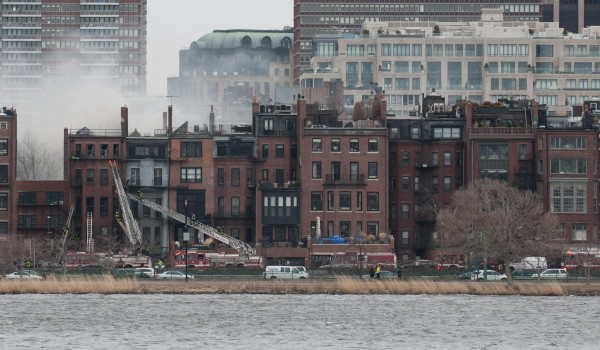 Smoke rises from across the Charles River above buildings on Beacon Street in Boston's Back Bay neighborhood as firefighters battled a fatal nine-alarm blaze in Boston, Massachusetts on Wednesday. Two firefighters were killed and several others were injured.