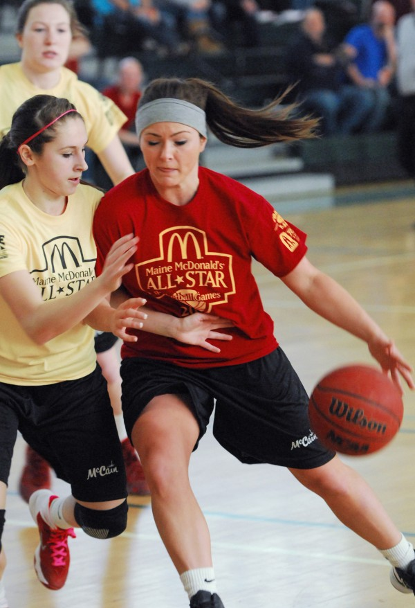 Nicole Moody of the West team tries to slow East player Kory Norcross during the Classes A/B game Saturday at the McDonald's East-West Senior All-Star Games at Husson University in Bangor.