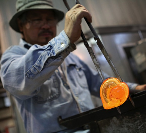 Somboun Vattana forms molten glass into a heart-shaped memento that will contain ashes of a deceased family member as a keepsake.