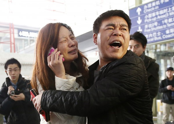 A relative (left) of a passenger on Malaysia Airlines flight MH370 cries as she talks on her mobile phone at the Beijing Capital International Airport on March 8, 2014. The Malaysia Airlines flight carrying 227 passengers and 12 crew lost contact with air traffic controllers early on Saturday en route from Kuala Lumpur to Beijing, the airline said in a statement.