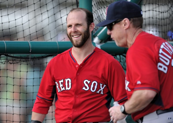 Boston Red Sox second baseman Dustin Pedroia (left) laughs with third base coach Brian Butterfield (right) during spring training Feb. 21 at JetBlue Park in Fort Myers, Fla.