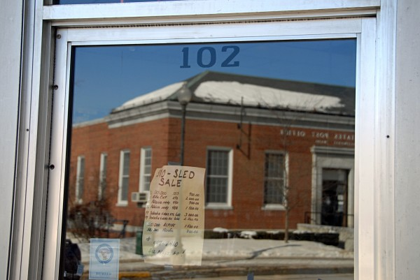 Millinocket's U.S. Post Office is reflected in the window at 102 Penobscot Ave., one of 25 properties town officials are selling to earn money.
