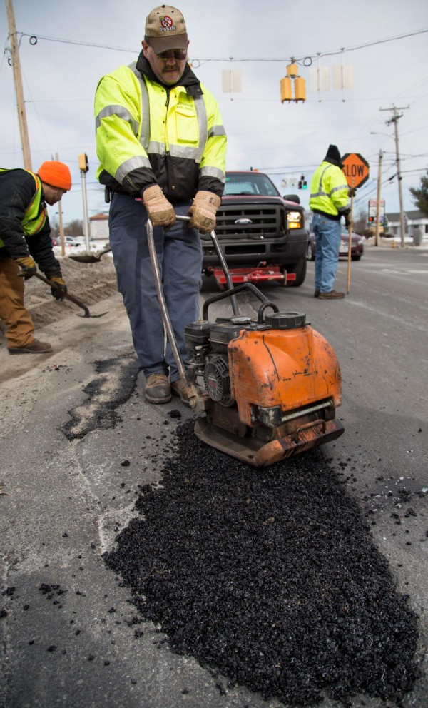 Mike Coffey, an employee of Falmouth's Public Works Department, uses a plate compactor to fill a large pothole Monday, March 3, on U.S. Route 1.