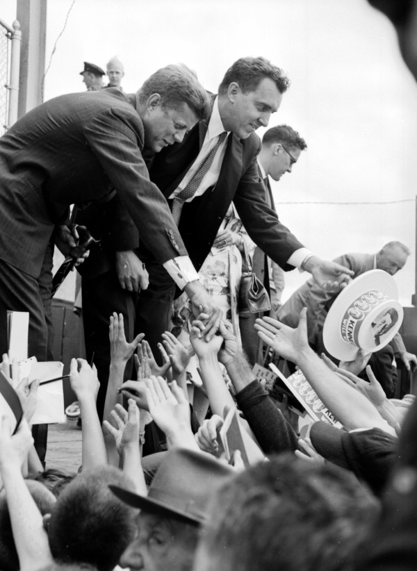 Senator John F. Kennedy reaches to shake hands with enthusiastic greeters following his address at the Bangor fairgrounds. At the candidate's left is Sen. Edmund S. Muskie of Waterville.