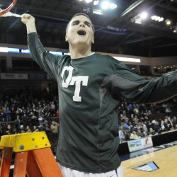 Old Town's Nicholas Cowan celebrates the Coyotes' win over Poland as he takes down a net after the Class B boys state championship game Friday night at the Cross Insurance Center in Bangor. Old Town won 64-39.