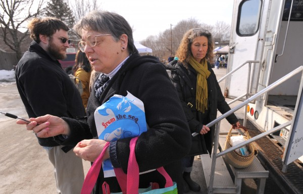 Julie Grab (left) of Old Town visits the Orono Winter Farmers' Market on Saturday.