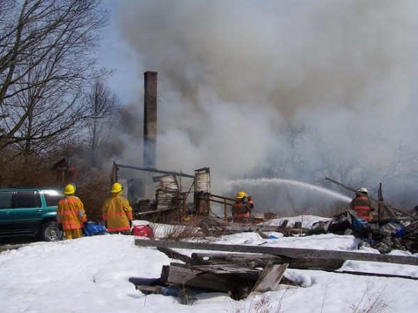 Firefighters continue to pour water where a blaze consumed an old house in Cooper on Saturday. The owner of the home suffered burns and was listed in critical condition on Sunday.