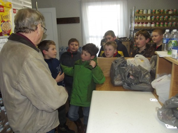 Art Carter of the Irene Chadbourne Ecumenical Food Pantry in Calais explains how the pantry operates to a group of boys raising money for an addition to the building. The boys are, from left, Kobe Saunders, Zachary Wentworth, Tristan Seavey, Ti Bennett, Jarrod McDonald (partly shown), Owen Brown, and Zachary Bridges.