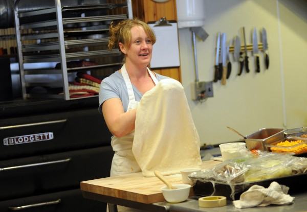 Kate Hogeland, part-time cook at the new Monroe General Store, prepares a hand-tossed pizza on Thursday.
