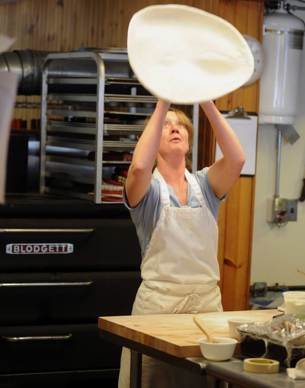 Kate Hogeland, part-time cook at the new Monroe General Store, makes hand-tossed pizza.