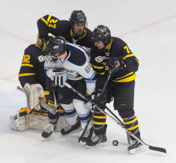 The University of Maine's Brian Morgan (center) battles for the puck with Merrimack College's Rasmus Tirronen (left) Jonathan Lashyn (right) and Justin Mansfield during their Hockey East  first-round playoff game Saturday evening at Alfond Arena in Orono.