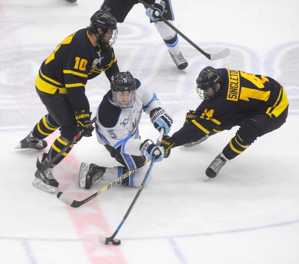 The University of Maine's Andrew Cerretani (center) battles for the puck with Merrimack College's Quinn Gould (left) and Kyle Singleton during their Hockey East first-round playoff game Saturday evening at Alfond Arena in Orono.