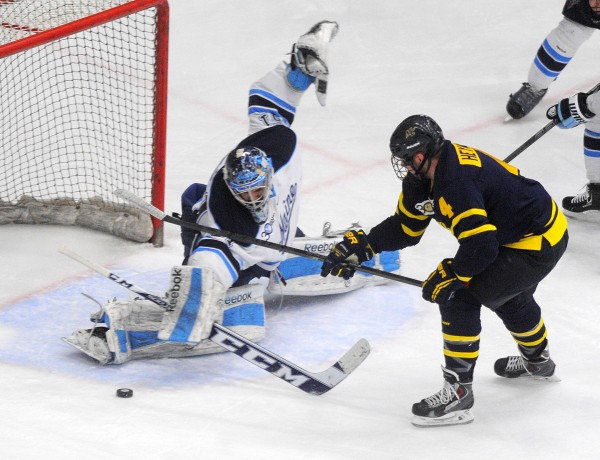 University of Maine goalie Martin Ouellette makes a save on a shot by Merrimack College's Jordan Heywood during their Hockey East first-round playoff game Saturday evening at Alfond Arena in Orono.