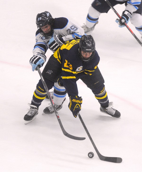 The University of Maine's Connor Leen (left) and Merrimack College's Josh Myers battle for the puck during their Hockey East  first-round playoff game Saturday evening at Alfond Arena in Orono.