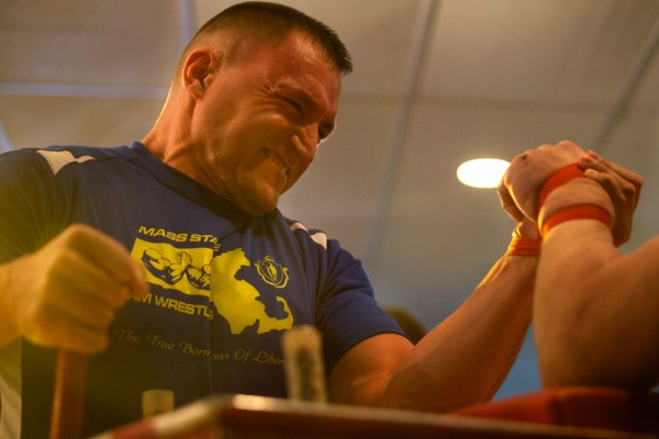 Chris Burns of Massachusetts arm wrestles with his hand strapped to his opponent Saturday in South Portland at the 2014 Maine State Armwrestling Championship.
