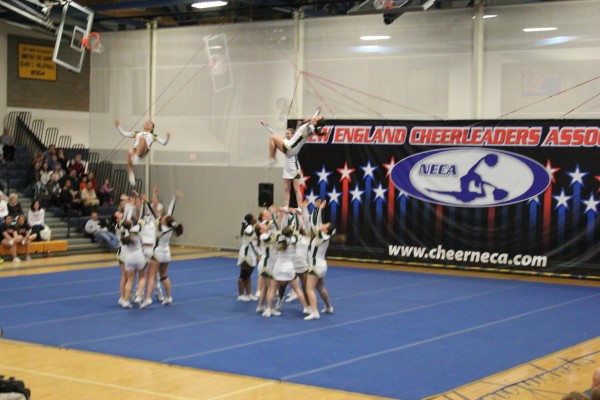 Husson University does an opening stunt that features two back-tuck tosses during the New England Cheerleading & Dance Team Open Championships Saturday in East Haven, Conn.
