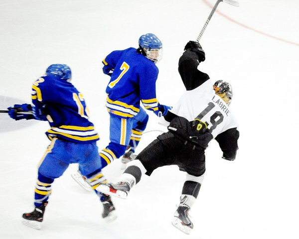 Caleb Labrie of Saint Dominic gets tripped up with Falmouth's Andre Clement (12) and Connor MacDowell (7) during the third period of the Class A state final on Saturday in Lewiston.