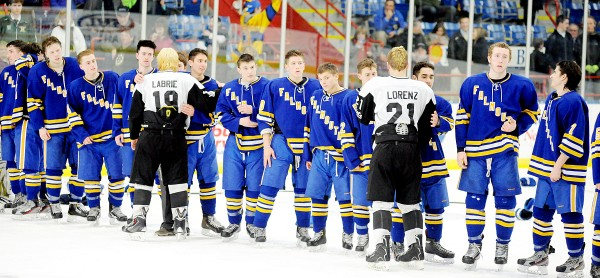 Saint Dominic players Caleb Labrie (19) and Mitch Lorenz (21) congratulate Falmouth players during the awards ceremony on Saturday after Falmouth won the Class A state final 3-2 in Lewiston.