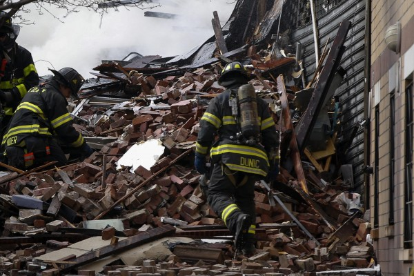 Firefighters go through debris and rubble at the site of a building collapse and fire in New York on Wednesday.