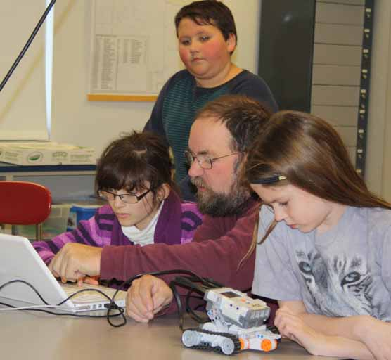 Mikaela Spooner (right) takes a look at her robot while teacher Ernie Easter and Morgan Dube work on the little robot's programming at the New Sweden School. Jordan Sandstrom (top) is also pictured looking in on the lesson.
