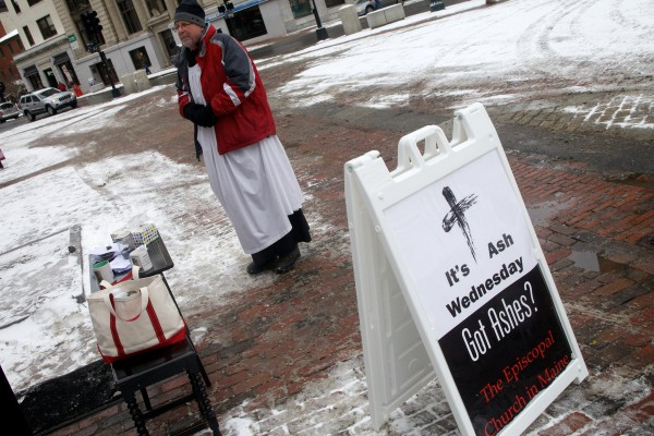 Episcopal priest Larry Weeks offers ashes to passersby on Ash Wednesday in Portland's Monument Square.